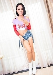 Ladyboy Bon sitting by the window in overalled jean shorts, a little pink shirt, and high heel white boots.