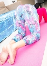 Ladyboy Pooky is wearing yoga gear and stretching on her pink mat.
